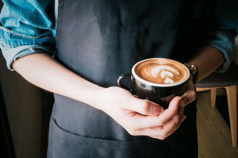 woman holding a cup of coffee americano in her hands