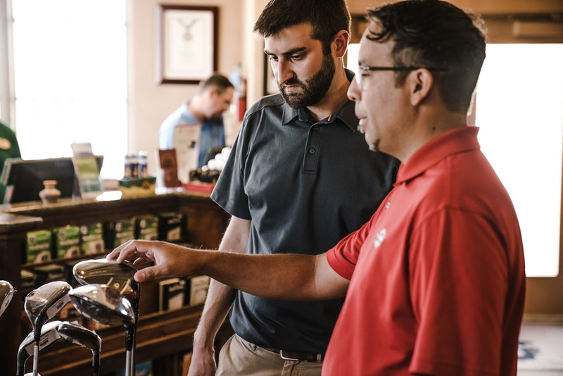 store manager trains an employee in a shop with golf gear