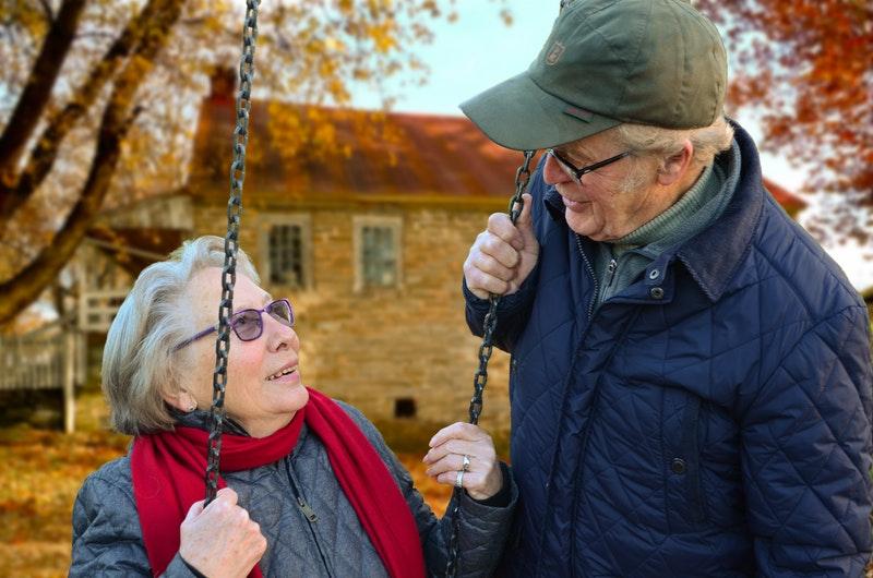 elderly couple is enjoying a sunny autumn day outside