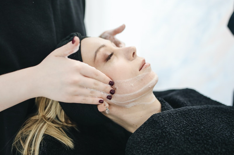 A woman is receiving treatment for the skin on her face. We can see the hands of the esthetician on the picture