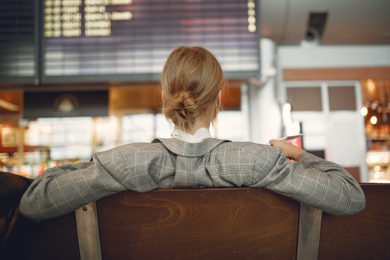 female business traveler sits in an airport hall, waiting for her flight