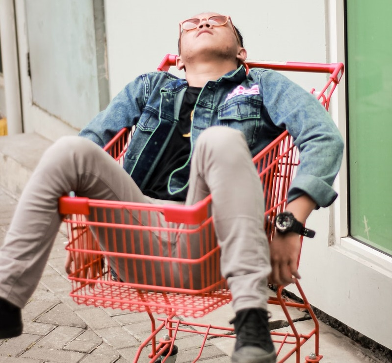 tired employee sleeps in a shopping cart