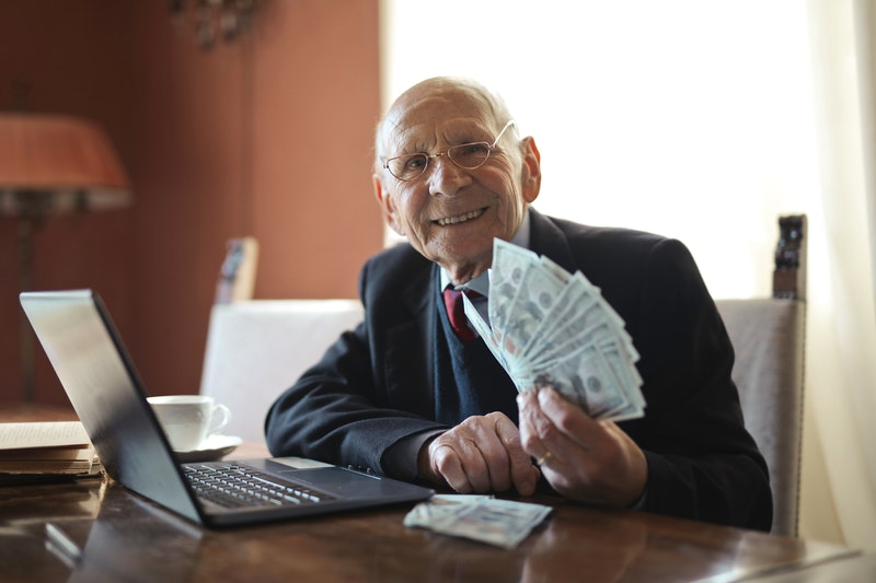 senior businessman holds a lot of cash in his hands