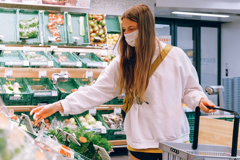 woman wearing a face mask shops at a big grocery store