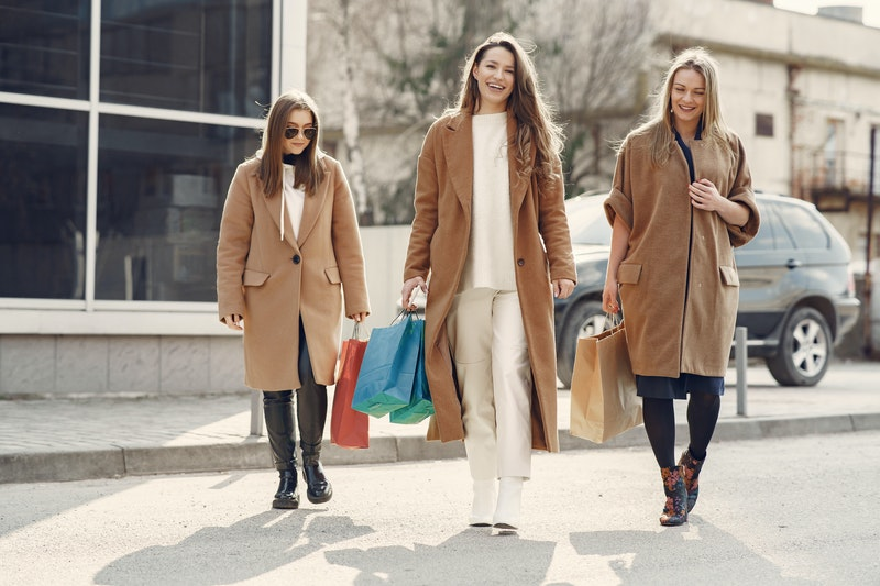 three satisfied female customers leave the store with their bags full